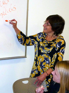 Nancy Steinberg Warren writing on a whiteboard.